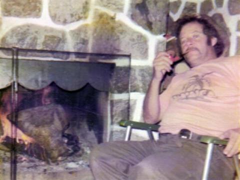 Yvon au chalet en face de son foyer en pierre naturelle qu'il a érigé lui-même en train de savourer une bonne pipe,1974-75.