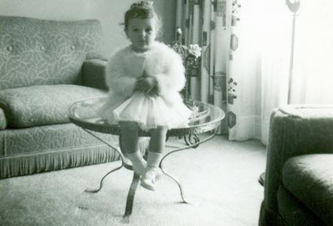 Christiane, 2 ans, assise sur une table de salon fabriquée par son père Yvon.