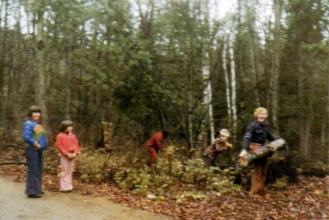 Jakel et son amie regardant Yvon au travail. Jacqueline assise sur une bûche, et Jocelyn soulevant un tronc au chalet.