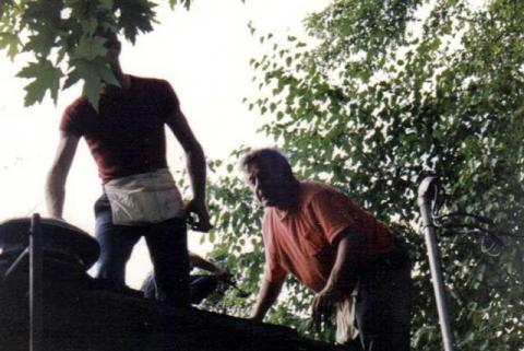 Jocelyn et Yvon recouvrant la toiture de sa maison.