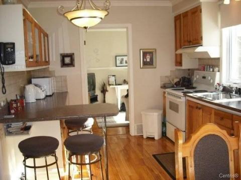La cuisine à air ouverte avec la salle de séjour.Plancher de bois, armoire, comptoir et tabourets en fer forgés font partis de ses oeuvres.